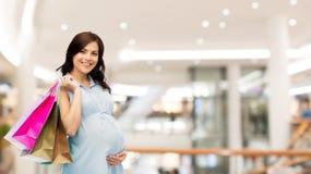 Glückliche schwangere Frau mit Einkaufenbeuteln lizenzfreies stockbild