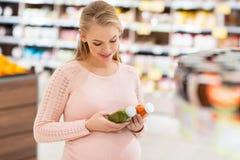 Glückliche schwangere Frau mit Saft am Gemischtwarenladen lizenzfreie stockbilder