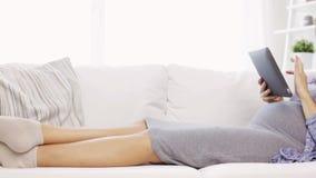 Glückliche schwangere Frau mit Tabletten-PC zu Hause stock video footage