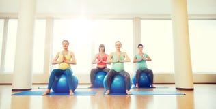 Glückliche schwangere Frauen, die auf fitball in der Turnhalle trainieren Lizenzfreie Stockfotos