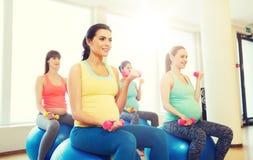 Glückliche schwangere Frauen, die auf fitball in der Turnhalle trainieren Lizenzfreies Stockbild