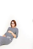 Glückliche schwangere Frauen sitzen auf Boden und Noten blähen auf stockfotografie