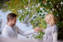 Glückliche schwangere Frauen und ihr Ehemann während des Wegs mit einem Mann nahe dem See Lizenzfreie Stockbilder