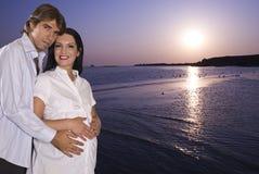 Glückliche schwangere Paare auf Strand am Sonnenaufgang Lizenzfreie Stockfotografie