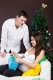 Glückliche schwangere Paare nähern sich dem Weihnachtsbaum Lizenzfreies Stockfoto