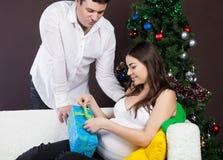 Glückliche schwangere Paare nähern sich dem Weihnachtsbaum Stockbilder