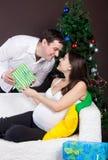 Glückliche schwangere Paare nähern sich dem Weihnachtsbaum Stockbild