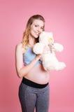 Glückliche Schwangerschaft, die Spielzeugbären umarmt Lizenzfreie Stockfotos