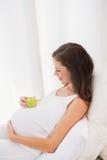 Glückliche Schwangerschaft mit einem Apfel auf seinem Bauch Lizenzfreies Stockbild