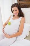 Glückliche Schwangerschaft mit einem Apfel auf seinem Bauch Stockbild