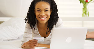 Glückliche schwarze Frau, die mit Laptop und Kreditkarte auf Bett lächelt lizenzfreies stockbild