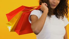 Glückliche schwarze Frau, die zurück Einkaufstaschen auf gelbem Hintergrund, Bargeld, Mode hält stock video