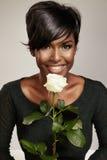 Glückliche schwarze Frau mit einer Rose lizenzfreie stockfotografie