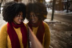 Glückliche schwarze Frau steht auf Straße nahe bei ihrer Reflexion im Fenster stockfotos