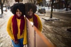 Glückliche schwarze Frau steht auf Straße nahe bei ihrer Reflexion im Fenster lizenzfreie stockbilder