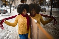 Glückliche schwarze Frau steht auf Straße nahe bei ihrer Reflexion im Fenster lizenzfreie stockfotos