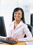 Glückliche schwarze Geschäftsfrau am Schreibtisch Lizenzfreie Stockfotos