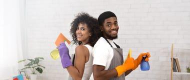 Glückliche schwarze Paare, die Reinigungsmittel während zu Hause säubern halten stockbild