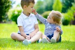 Glückliche Schwester und Bruder zusammen im Park lizenzfreie stockbilder