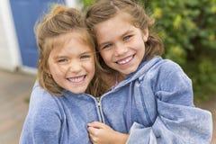 Glückliche Schwestern auf dem Strand mit den gleichen Kapuzenpullis Stockfotos