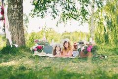 Glückliche Schwestern, die draußen auf einer Decke auf einem sonnigen Sommer liegen Lizenzfreie Stockbilder
