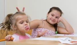 Glückliche Schwestern, die in Küche zeichnen Lizenzfreie Stockfotos