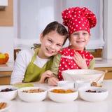 Glückliche Schwestern, die zusammen kochen Stockbild
