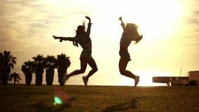 Glückliche Schwestern oder Freunde, die auf den Strand genießt Sonnenuntergang springen stock footage