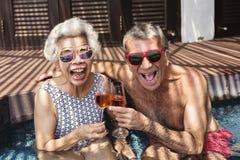 Glückliche Senioren, die prosecco im Pool trinken stockbilder