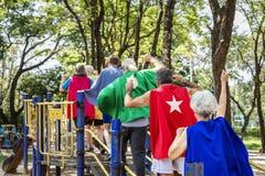 Glückliche Senioren, die Superheldkostüme an einem Spielplatz tragen stockfotografie