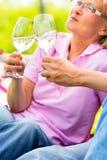 Glückliche Senioren, die trinkenden Wein des Picknicks essen Stockfotografie