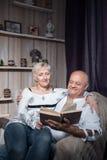 Glückliche Senioren verbinden das Sitzen im Stuhl und lesen Buch; lizenzfreie stockfotos