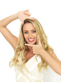 Glückliche sexy junge Frau, die durch die Gestaltung ihres Gesichtes mit ihren Händen aufwirft Lizenzfreie Stockbilder