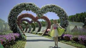 Glückliche sexy junge Frau mit rosa Blume geht auf Fußweg im Blumengarten Nettes Mädchen in der lustigen Spitze recht träumen stock video footage