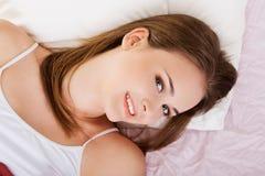 Glückliche sinnliche Frau, die im Bett liegt lizenzfreie stockfotografie