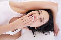 Glückliche sinnliche junge Frau, die im Bett liegt Stockbilder