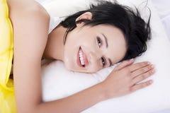 Glückliche sinnliche junge Frau, die im Bett liegt Lizenzfreie Stockbilder