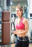 Glückliche Sitzfrau, die rosa Eignungs-BH beim Trainieren an der Turnhalle trägt Stockfotos
