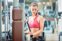 Glückliche Sitzfrau, die rosa Eignungs-BH beim Trainieren an der Turnhalle trägt Lizenzfreie Stockbilder