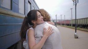 Glückliche Sitzung, frohe junge Frau umarmt Mann und lacht nahe Zuglastwagen auf Bahnhof nach Trennung stock video footage