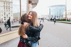 Glückliche Sitzung von zwei Freunden, die in der Straße umarmen Lizenzfreie Stockfotos
