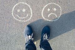 Glückliche smiley oder unglücklich, Text auf Asphaltstraße lizenzfreie stockfotografie