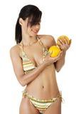 Glückliche Sommerfrau im Bikini mit Orangen. Stockfotos