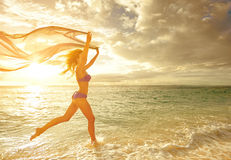 Glückliche sorglose Frau, die in den Sonnenuntergang auf dem Strand läuft lizenzfreie stockfotos