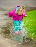 Glückliche Spiele des kleinen Mädchens in einer Pfütze lizenzfreie stockfotos