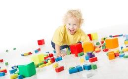 Glückliche spielende Blöcke des Kindes über Weiß Stockbild