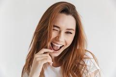 Glückliche spielerische Frau in der zufälligen Kleidung blinzelt ihr Auge Lizenzfreies Stockfoto