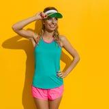 Glückliche Sport-Frau im Sonnenlicht gegen gelben Hintergrund Stockbild