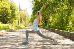 Glückliche Sportfrau, die Laufleinen mit Dummköpfen im Park im Th tut Lizenzfreie Stockfotos