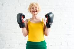glückliche sportliche ältere Frau beim Boxhandschuhlächeln stockfotos